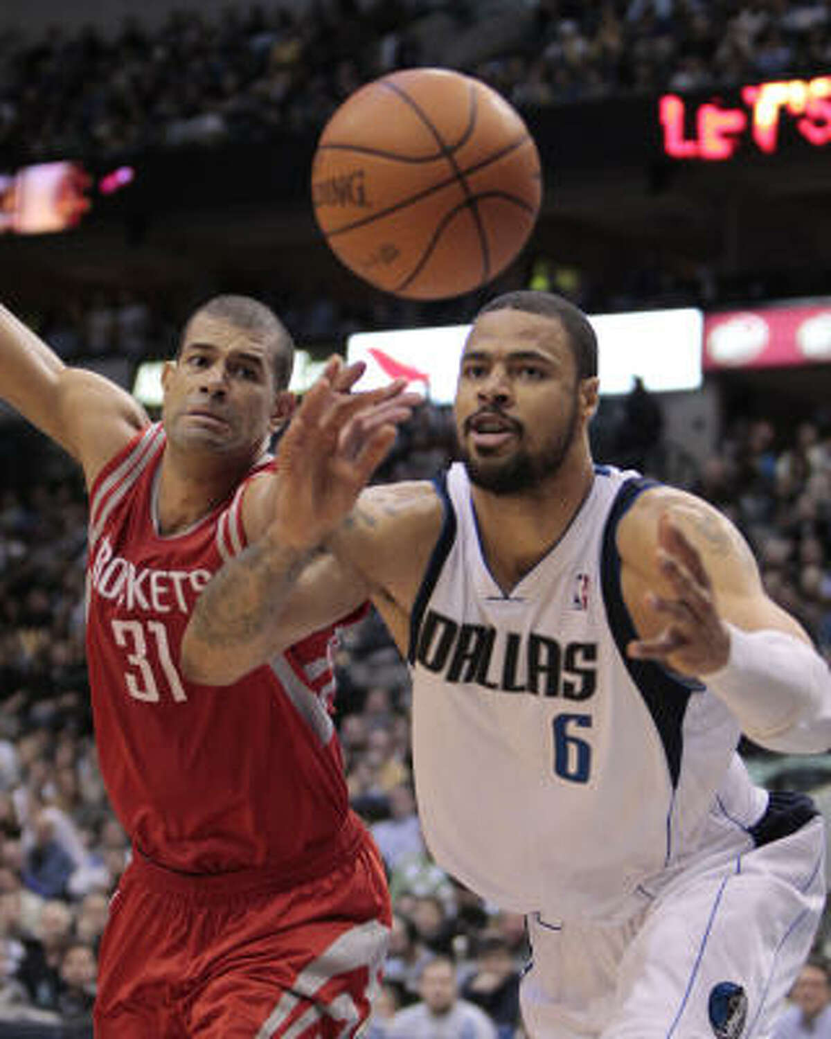 Mavericks center Tyson Chandler (6) and Rockets forward Shane Battier chase for a loose ball during the second half.