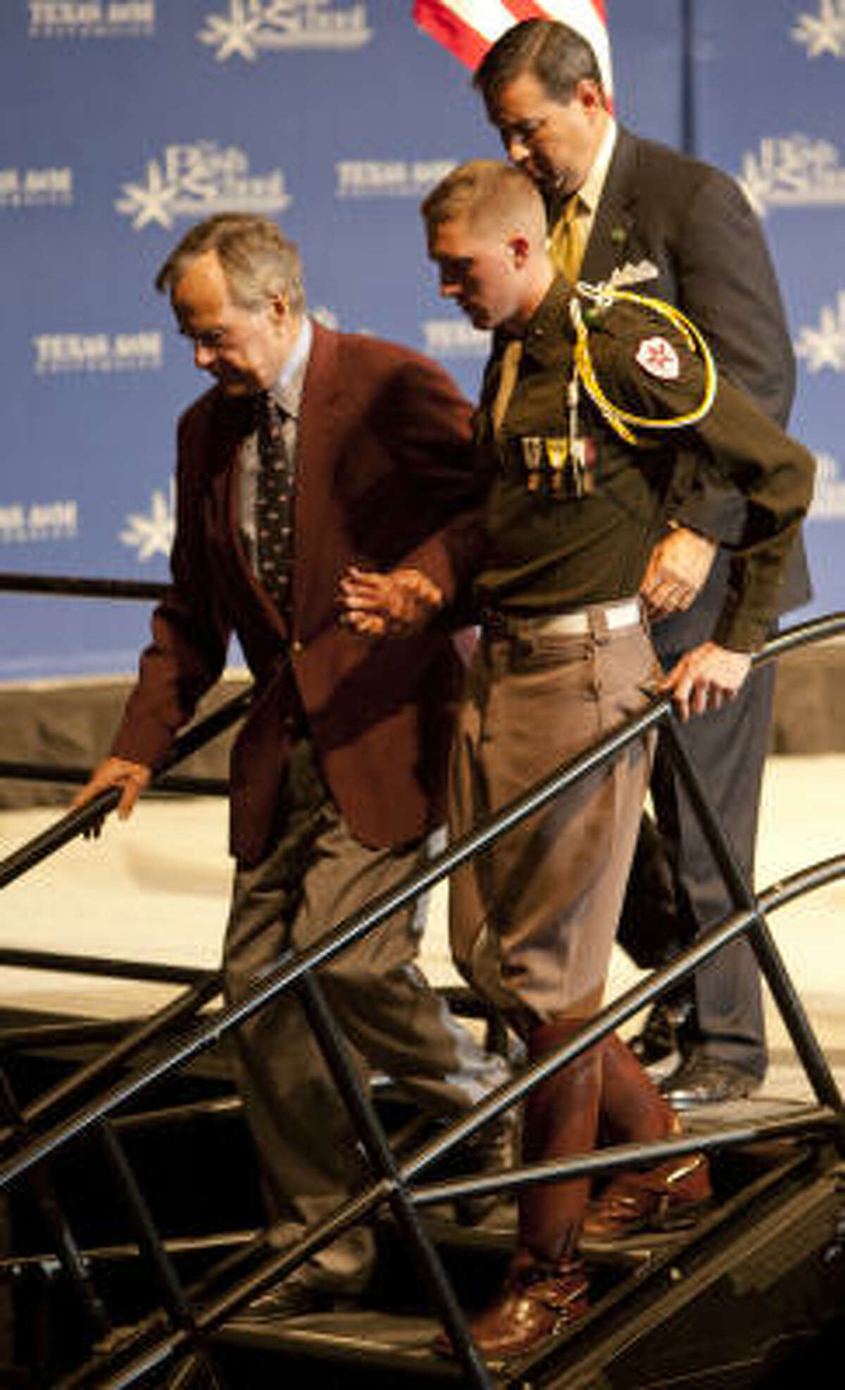 President George Bush is assisted by a Cadet as he walks to his seat during the 20th Anniversary Commemoration of the beginning of military operations to liberate Kuwait.
