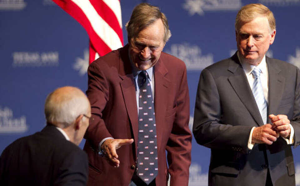 President George Bush extends his hand to former Secretary of Defense and Vice President Dick Cheney