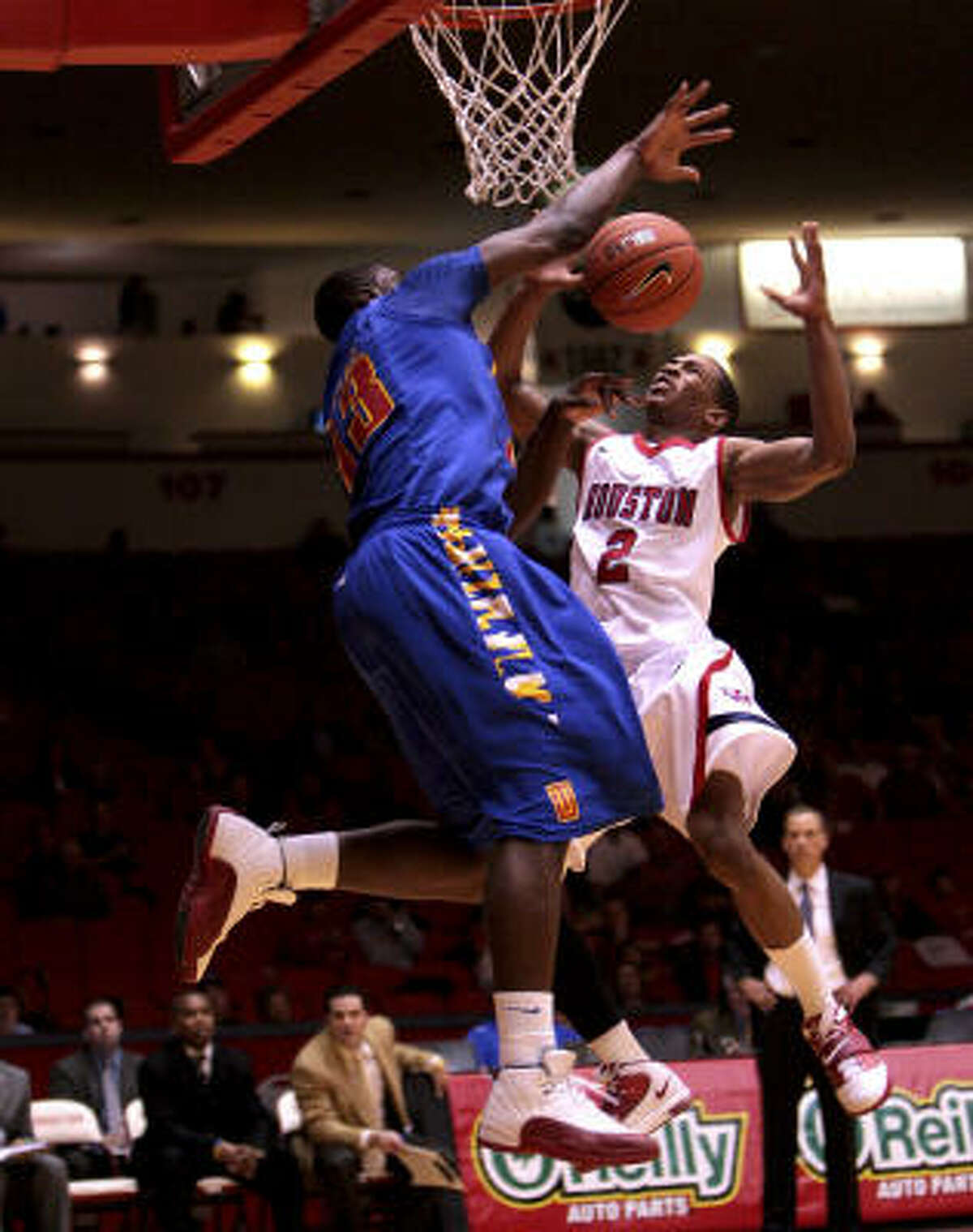 UH guard Zamal Nixon (2) takes a hard foul from Tulsa's Joe Richard as he drives to the basket during the first half.