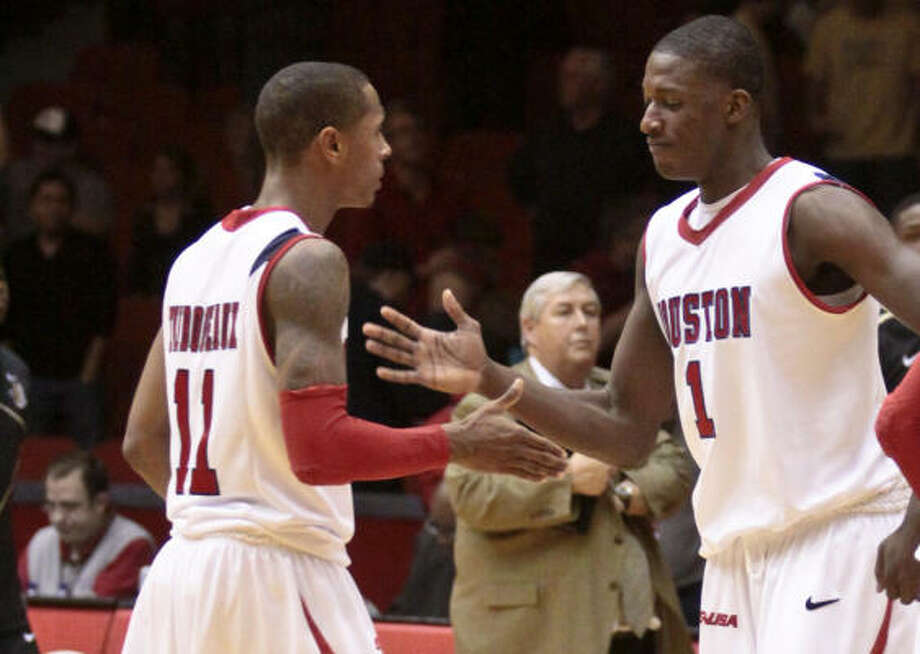 Houston players Darian Thibodeaux (11), left, and Mikhail McLean (1) celebrate their win against Central Florida. Photo: Eric Kayne, For The Chronicle