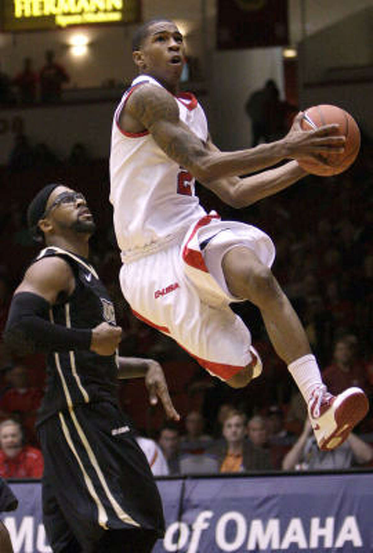 Houston's Zamal Nixon (2) drives the basket past Central Florida's Marcus Jordan (5) for a layup.