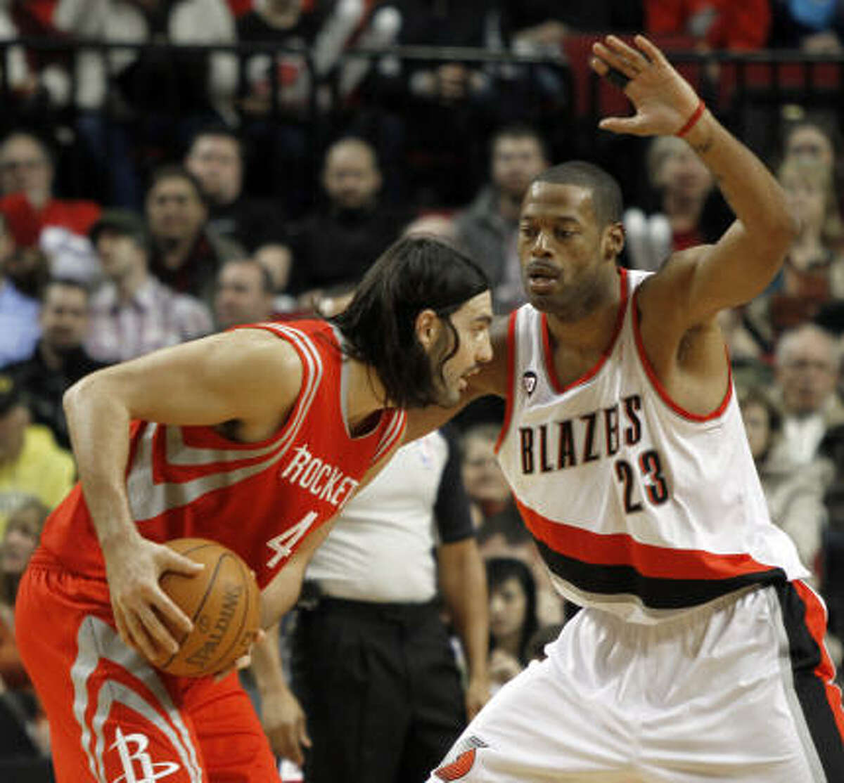 Rockets forward Luis Scola, left, looks for room against Trail Blazers center Marcus Camby.
