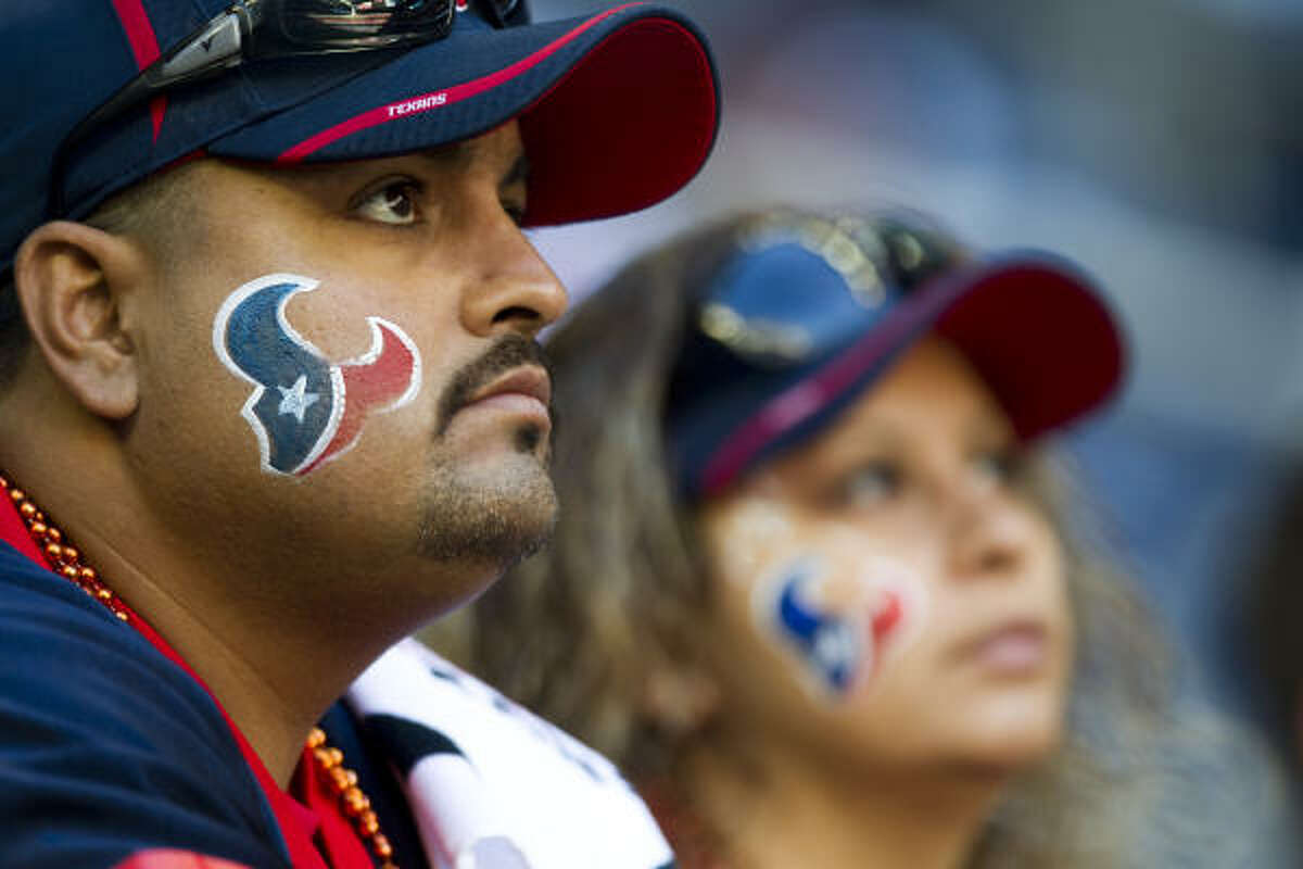 Texans fans Hector Vega, left, and Norma Moreno watch pre-game warmups.