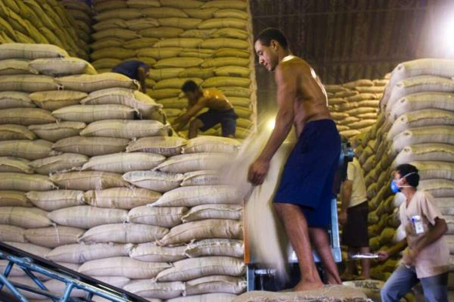 Workers belonging to Brazil's largest coffee cooperative move sacks of beans in Guaxupe. The driest winter in two decades will likely reduce the country's production. Photo: MARCOS ISSA, BLOOMBERG NEWS