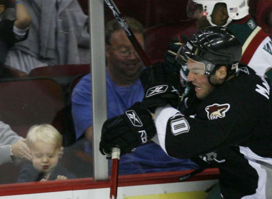 A woman covers a child's ears as San Antonio Rampage center Donald MacLean checks Aeros right wing Joel Ward, right, into the boards at Toyota Center. Photo: Kevin Fujii, Chronicle