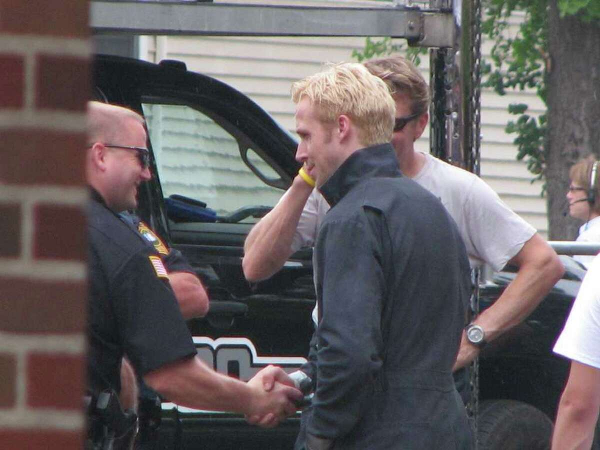 Ryan Gosling shakes a police officers hand during a break in filming of