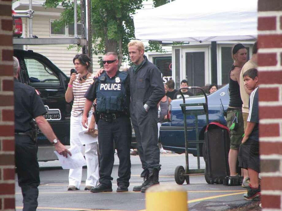 "Ryan Gosling poses with a police officer during a break in filming of ""The Place Beyond the Pines"" on Friday, July 29. The day's filming was being carried out outside the First National Bank of Scotia branch in Scotia. (Desiree LaBombard / Special to the Times Union)"