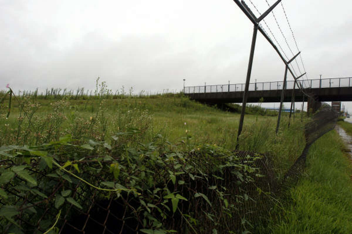 The pedestrian and tramway bridge on the former site of Six Flags AstroWorld is now surrounded by overgrown weeds.