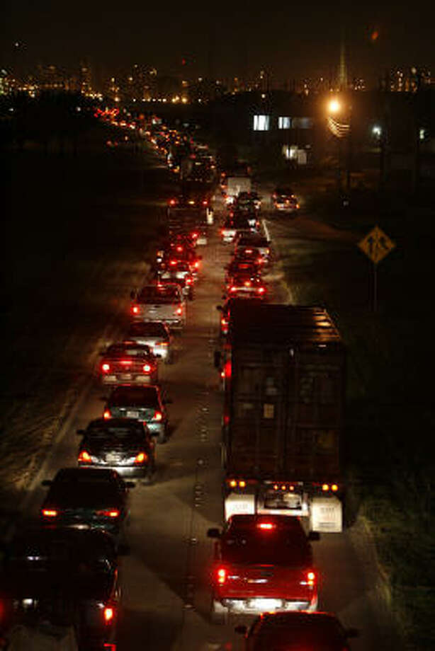 Traffic along Texas 225 westbound moves slowly along the feeder after the highway was closed Thursday in Deer Park after a moisture-density gauge containing two sources of radiation fell off the back of a pickup truck and broke into pieces about 3:50 p.m. Photo: James Nielsen, Chronicle