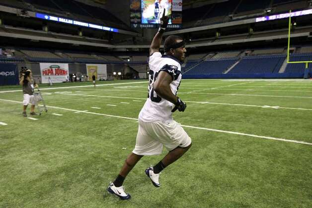 Receiver Dez Bryant reacts after making a throw from mid-field toward the goal post at the conclusion of the morning session of the Dallas Cowboys training camp at the Alamodome on Friday, July 29, 2011. His throw clanked off the lower stanchion. Kin Man Hui/kmhui@express-news.net Photo: KIN MAN HUI, SAN ANTONIO EXPRESS-NEWS / SAN ANTONIO EXPRESS-NEWS