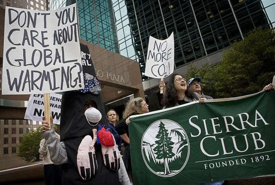 """Margie Diddams, left, dressed in a """"coal monster"""" suit, and Evelyn Sardina, holding the Sierra Club banner, protest outside Dynegy's downtown headquarters on Wednesday. The Sierra Club has launched a national campaign against the use of coal-fired power plants. Photo: ERIN TRIEB, FOR THE CHRONICLE"""