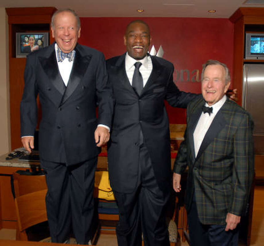 Houston Rockets owner Leslie Alexander grew many inches by standing on a chair at the Tux & Tennies gala reception at Toyota Center where Dikembe Mutombo and former President George H.W. Bush were special guests. Photo: Dave Rossman, For The Chronicle