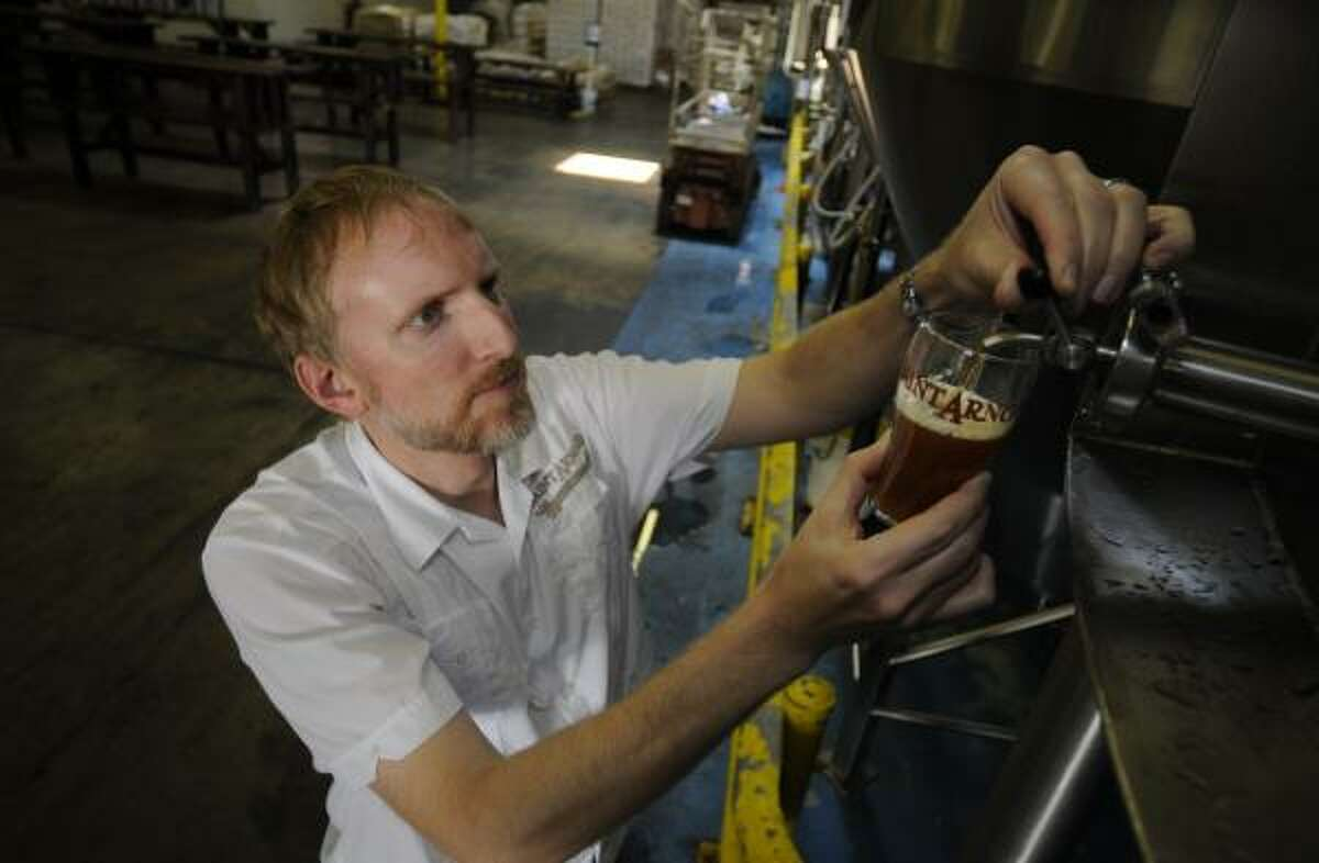 Brock Wagner, owner and brewmaster of Saint Arnold Brewing Co., pours a sample from one of the company's tanks.