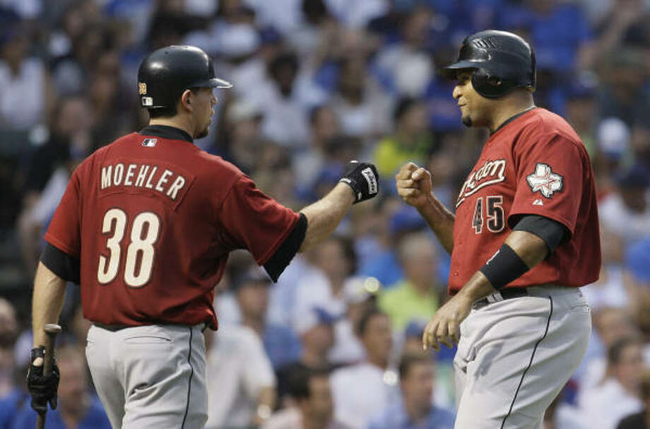 Carlos Lee, right, is congratulated by Brian Moehler as he scores on a bases-loaded walk during the fourth inning. Photo: M. Spencer Green, AP