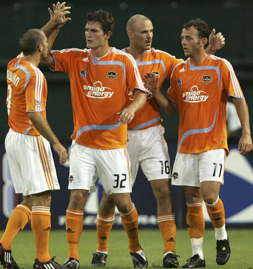 Houston Dynamo's Bobby Boswell (32), Craig Waibel (16), Brad Davis (11) and Brian Mullan celebrate the Dynamo's success in the SuperLiga international tournament. Photo: Lawrence Jackson, AP