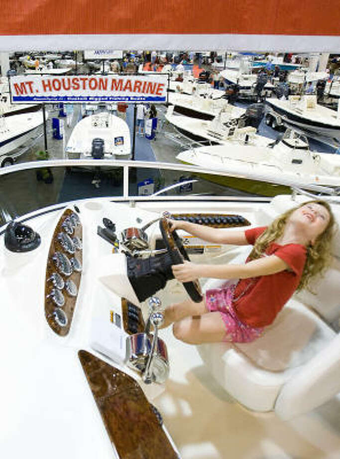 Sage Pollock, 6, pretends to drive one of the boats on display Saturday at the Houston International Boat, Sport & Travel Show at the Reliant Center. Photo: Nick De La Torre, CHRONICLE