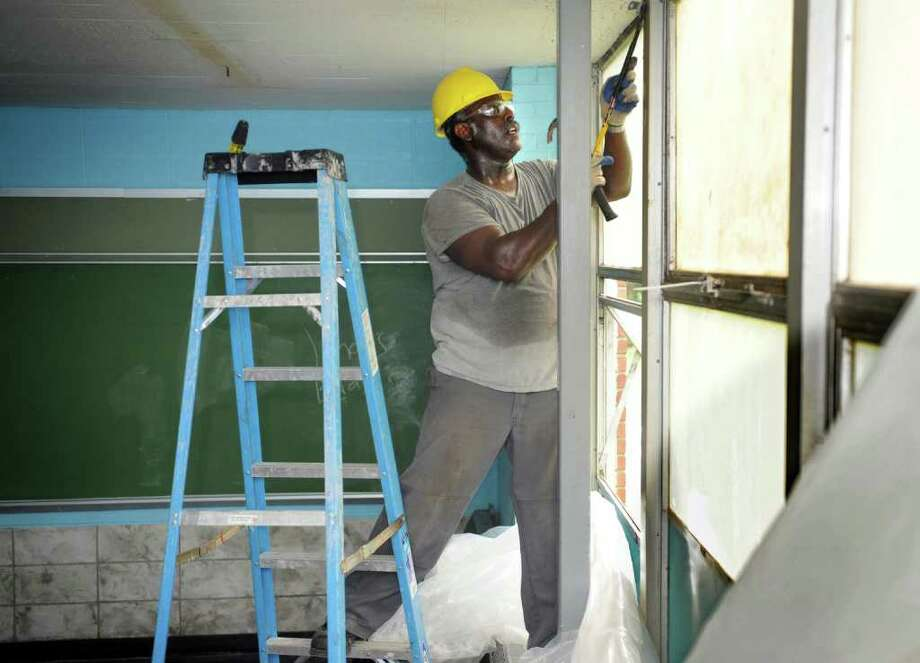Ronald Patton works on sealing up a classroom for asbestos removal Friday, July 29, 2011 at Wilbur Cross School in Bridgeport, Conn.  Patton was previously unemployed but found work after completing the Green-Up Bridgeport Training program. Photo: Autumn Driscoll / Connecticut Post