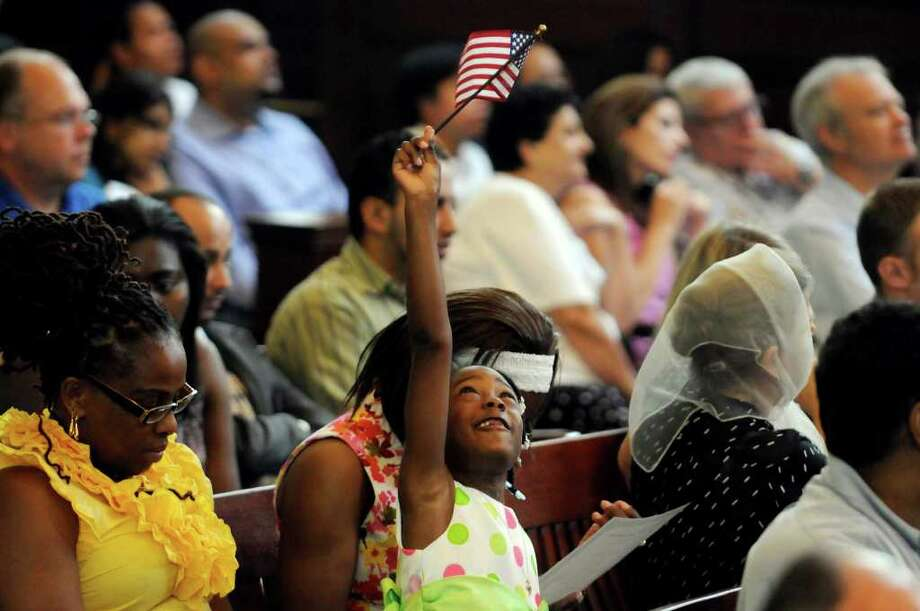 Victoria Rucker, 6, of Albany waves the American flag as her mother, Pauline Rucker, a native of Jamaica, becomes a citizen of the United States during a naturalization ceremony for 65 new U.S. citizens at the Rensselaer County Courthouse in Troy, NY, on Friday, July 29, 2011.( Michael P. Farrell/Times Union) Photo: Michael P. Farrell