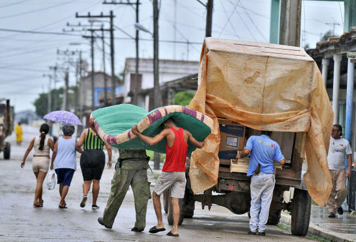 People carry their personal belongings in an effort to seek shelter from the oncoming Hurricane Gustav Saturday in Surgidero de Batabano, 45 miles south of Havana.
