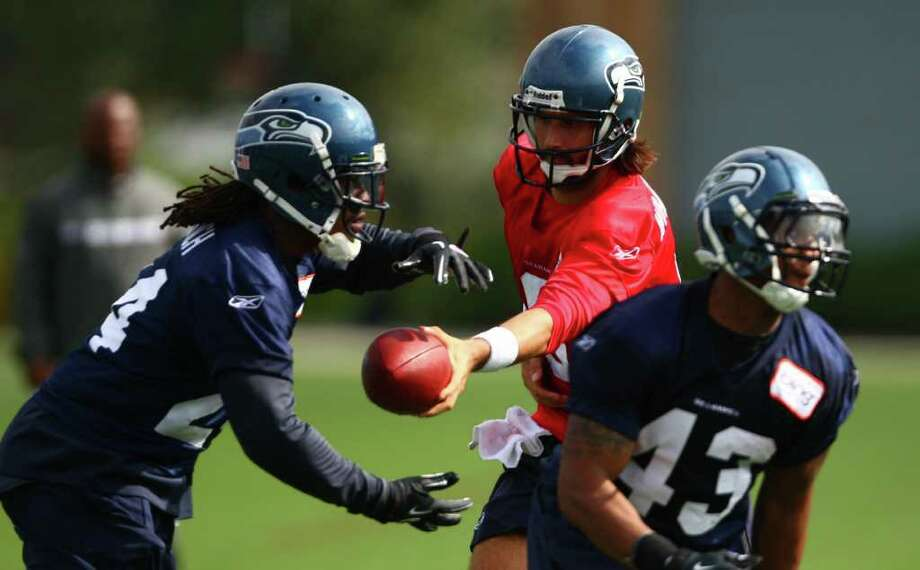 Quarterback Charlie Whitehurst hands the ball to Marshawn Lynch. Photo: JOSHUA TRUJILLO / SEATTLEPI.COM
