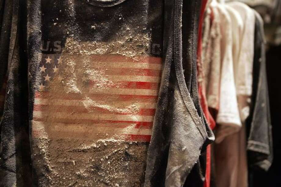 An American flag T-shirt covered in ash and dust from the destroyed World Trade Center towers is seen at the Elegy in the Dust: September 11th and the Chelsea Jeans Memorial exhibit at the New York Historical Society. The exhibit features racks of clothes covered in dust from the Chelsea Jeans store in that were preserved by owner David Cohen as a memorial. Photo: Mario Tama, Getty Images