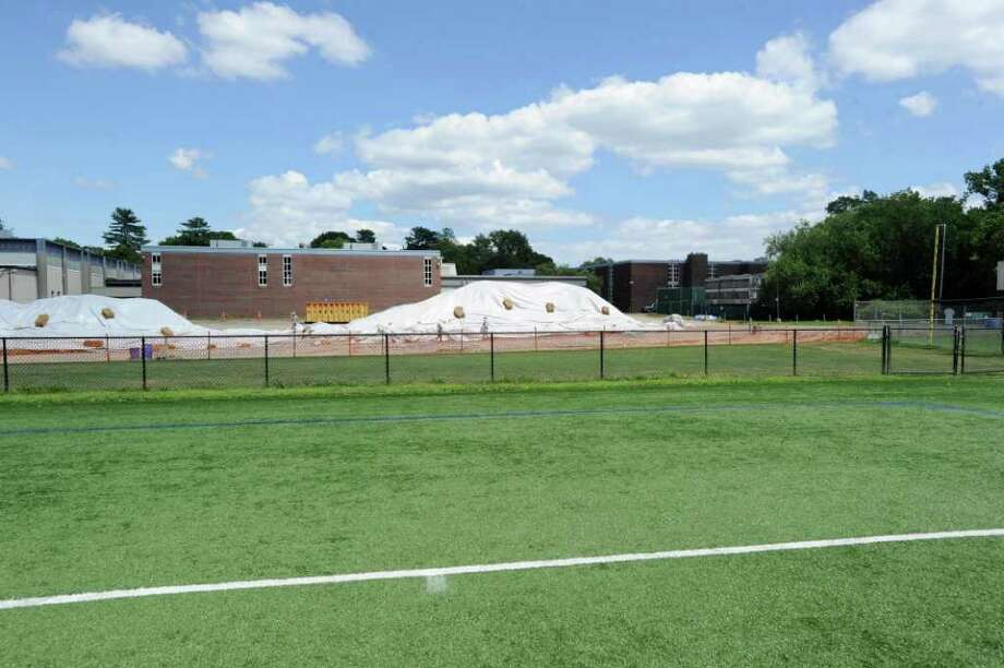School officials announced all Greenwich High School playing fields would be closed immediately Friday after testing discovered PCB toxins that exceed regulatory standards near fields 3 and 4. District officials began testing soil samples after workers on the school's new auditorium project discovered contaminated soil earlier this month. Pictured is the artificial turf field to the west of the school Wednesday, July 27, 2011, with the excavation site in the background. Photo: Bob Luckey