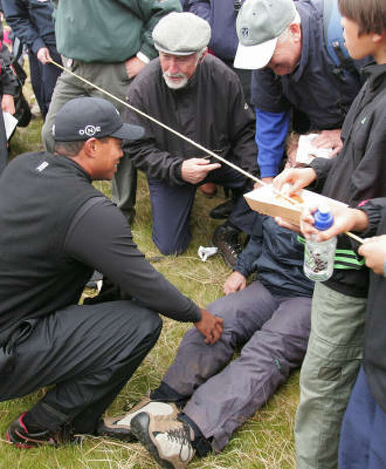 Tiger Woods checks on a woman after she was hit in the head by his ball on the 6th hole. Photo: CARL DE SOUZA, AFP/Getty Images
