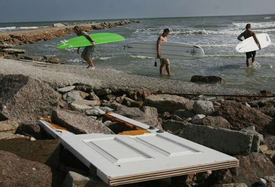 Surfers Pat McClain, Sam Bertron and Alek Rockrisc return to the coast after a ban was lifted from swimming and surfing along the Seawall a month after Hurricane Ike on Monday. Photo: MAYRA BELTRÁN, CHRONICLE