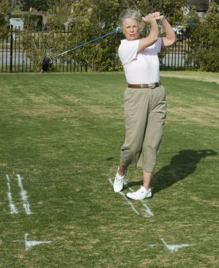 Betsy Cullen demonstrates the correct line to finish a golf swing. Photo: Brett Coomer, Chronicle