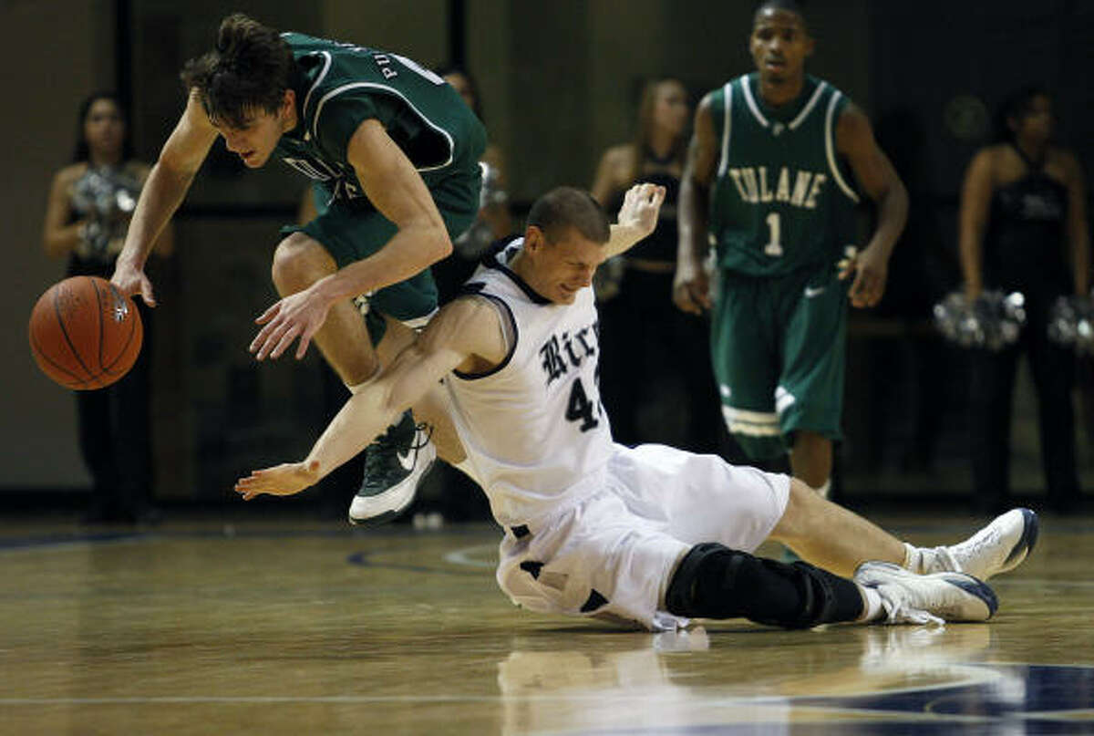 Tulane's Daniel Puckett (left) and Rice's Aleks Perka get tripped up while going after a loose ball.