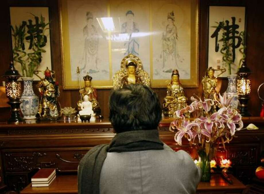 Hsui Hui Wang, owner of the Red Carpet Inn and Bodhi's Zen Garden and Veggie restaurant, blesses an altar after entering a meditation room at the hotel. Photo: JOHNNY HANSON PHOTOS, CHRONICLE