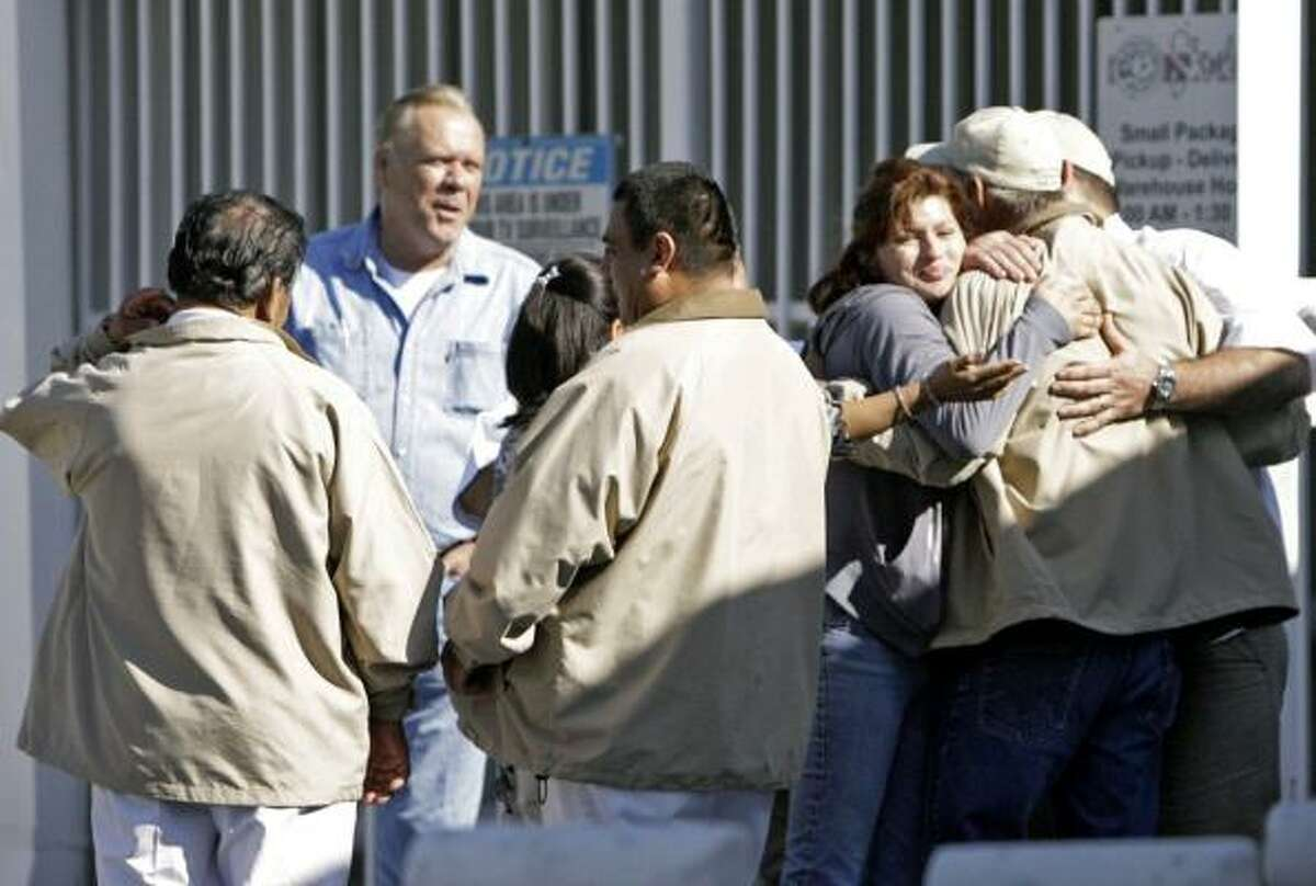 Employees at the Shipley Do-Nuts headquarters on Houston's north side take a moment to regroup Wednesday after 20 of their co-workers were taken away by federal immigration agents in a 5 a.m. raid.