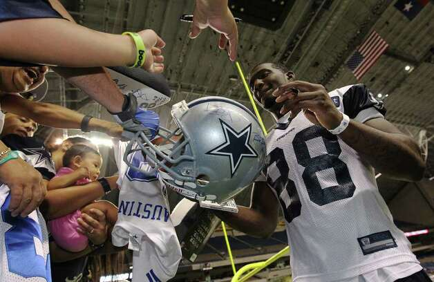 Receiver Dez Bryant signs autographs for fans at the conclusion of the afternoon session of the Dallas Cowboys training camp at the Alamodome on Friday, July 29, 2011. Kin Man Hui/kmhui@express-news.net Photo: KIN MAN HUI, : / SAN ANTONIO EXPRESS-NEWS
