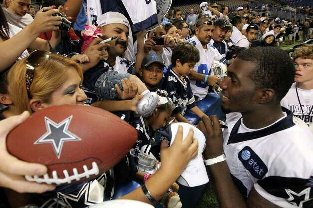 Receiver Dez Bryant thrills fans during an autograph session after the afternoon session of the Dallas Cowboys training camp at the Alamodome on Friday, July 29, 2011. Bryant signed an autograph on the jersey of six-month-old Rio Grande Valley resident Jennica Solis who was held by her father, Javier, during the session. (Kin Man Hui/kmhui@express-news.net Photo: KIN MAN HUI, : / SAN ANTONIO EXPRESS-NEWS