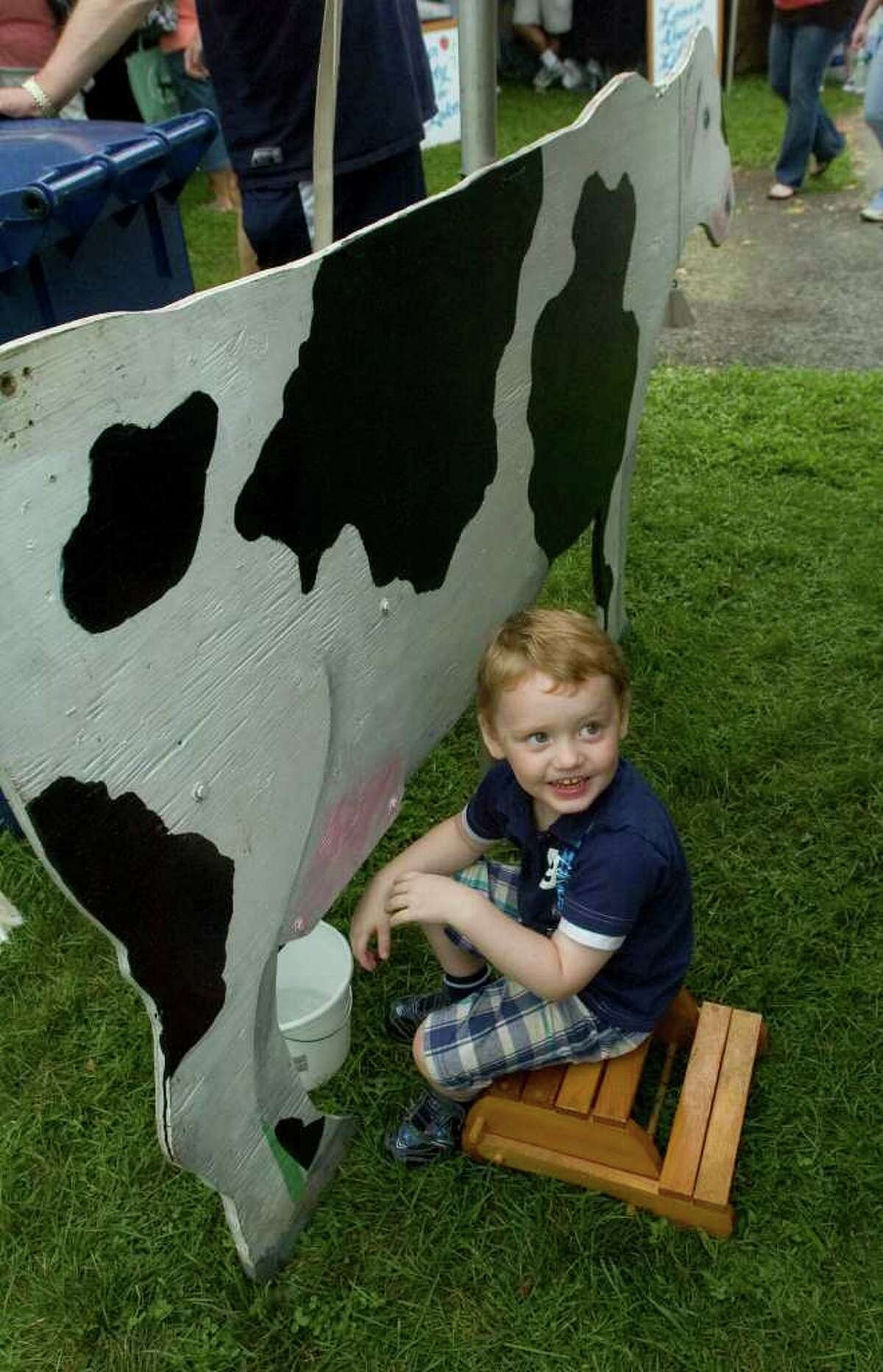 Benjamin Larmore, 4, looks to his mother after demonstrating how to milk a cow at the Sunny Valley Preserve booth that is part of The Nature Conservancy during the 44th Annual New Milford Village Fair Days on Friday, July 29, 2011.