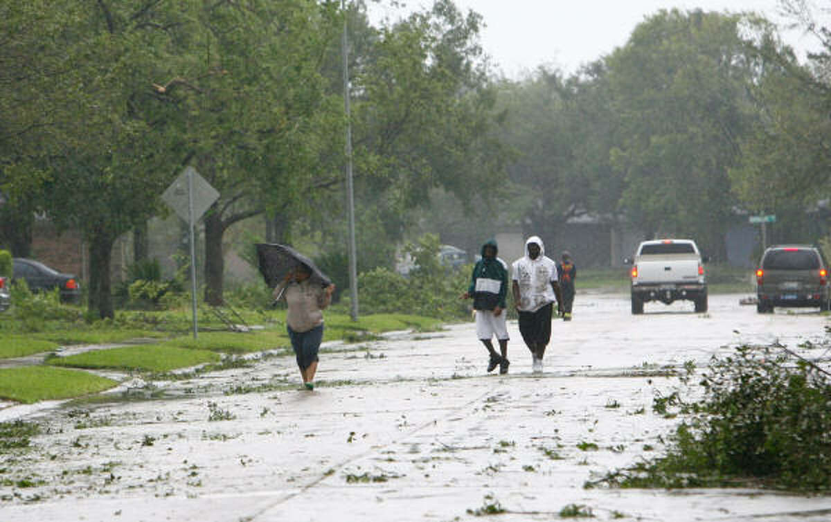 People walk to assess neighborhood damage in Pearland this morning after Hurricane Ike made landfall. Harris County Judge Ed Emmett urged residents to stay in their homes and conserve water today as officials assess the damage dealt by Ike.