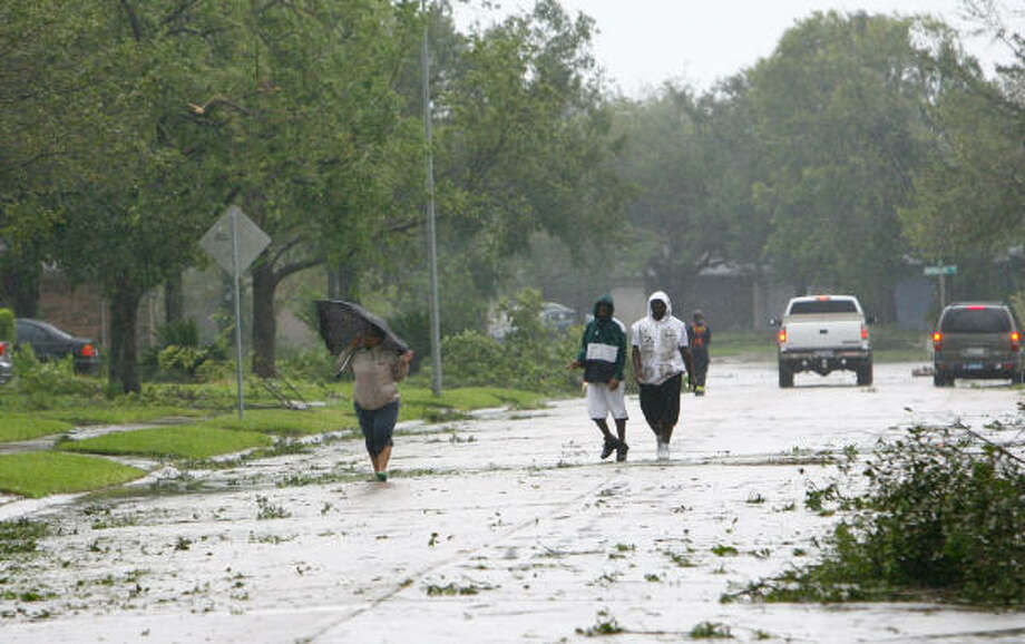 People walk to assess neighborhood damage in Pearland this morning after Hurricane Ike made landfall. Harris County Judge Ed Emmett urged residents to stay in their homes and conserve water today as officials assess the damage dealt by Ike. Photo: Nick De La Torre, CHRONICLE