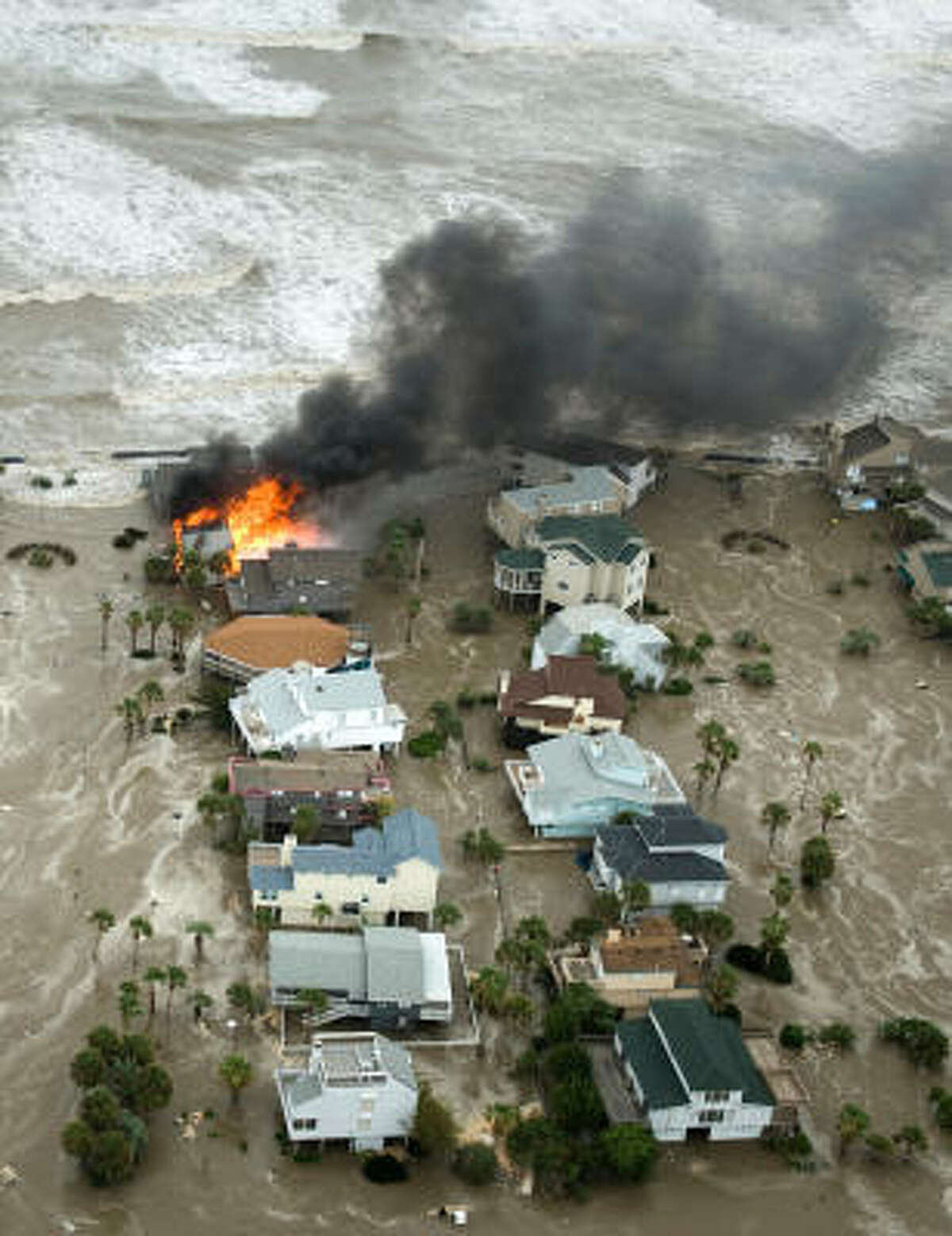 A house is engulfed in flames as floodwaters and crashing waves inundated beach homes on Galveston Island as Hurricane Ike approaches the Texas Gulf Coast on Friday.
