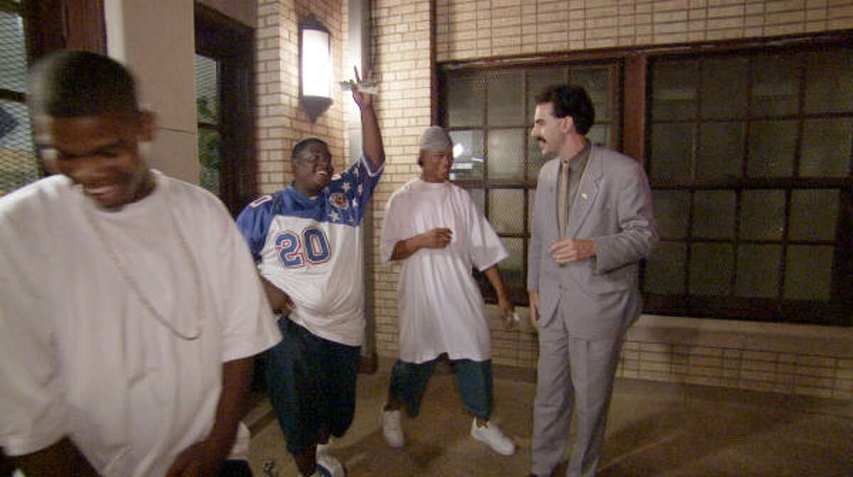 Borat (Sacha Baron Cohen), right, learns some street slang from an American gang.
