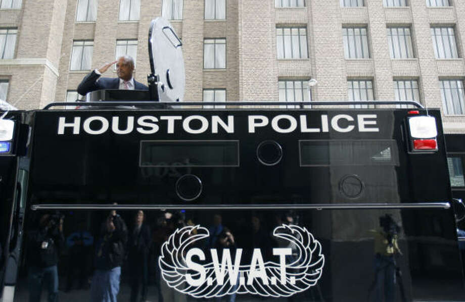 Houston Police Chief Harold Hurtt salutes from the turret of HPD's new SWAT truck at police headquarters in downtown Houston on Thursday. Photo: Karen Warren, Chronicle