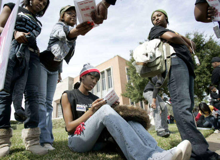 Chantea Cooper, seated, reads campaign literature as she and other Prairie View A&M University students wait to vote after a 2½-hour march to the Waller County Courthouse in Hempstead on Tuesday. Photo: Paul Zoeller, FOR THE CHRONICLE