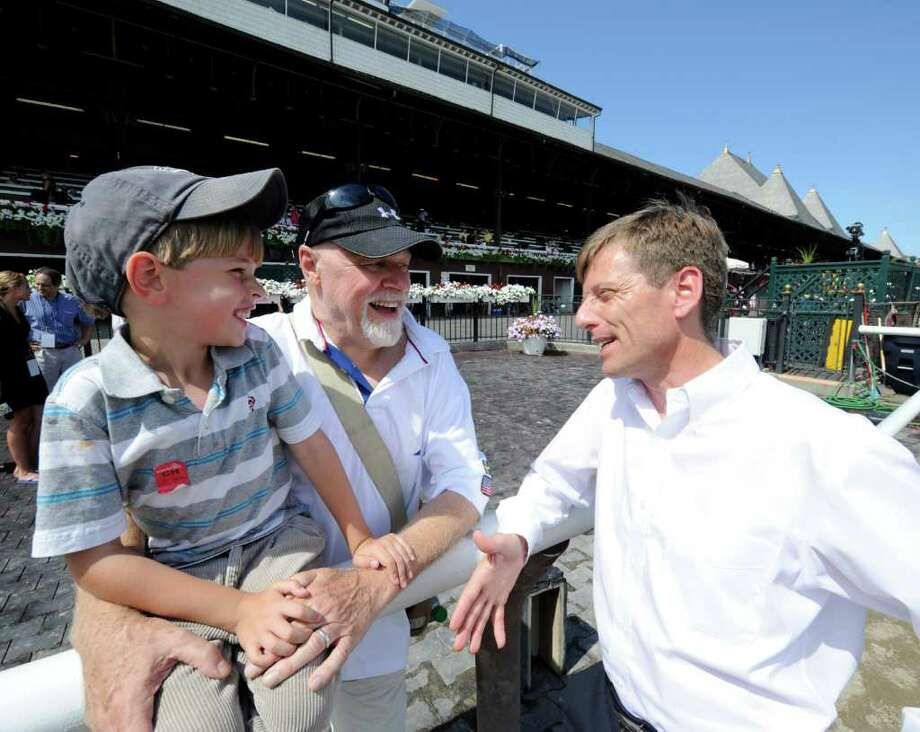 Retired jockey Richard Migliore, right, works with fans at the Saratoga Race Course in Saratoga Springs, N.Y. July 28, 2011.   (Skip Dickstein / Times Union) Photo: SKIP DICKSTEIN / 1001406A