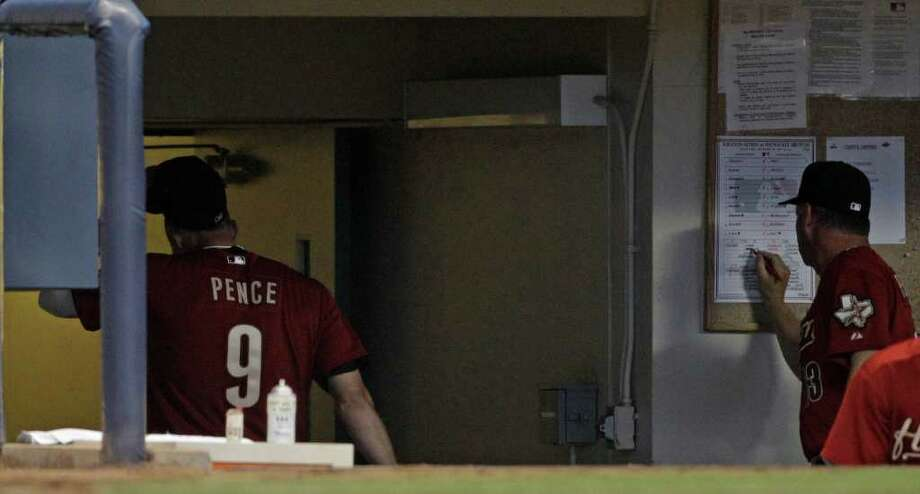 Houston Astros' Hunter Pence walks into the clubhouse as bench coach Al Pedrique changes the lineup after Pence was taken out of the game during the fifth inning of a baseball game against the Milwaukee Brewers Friday, July 29, 2011, in Milwaukee. Pence has been pulled from the game amid reports he's been traded to the Philadelphia Phillies. (AP Photo/Morry Gash) Photo: Morry Gash
