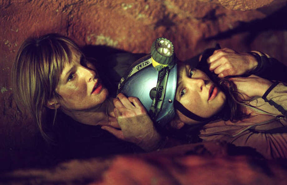 Rebecca (Saskia Mulder, left) and Sam (MyAnna Buring) fight for their lives in a dark cave, in The Descent. Photo: Courtesy Photo