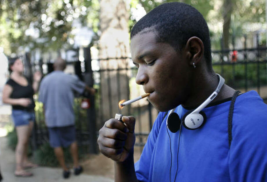 Elana Arthur, 21, lights a cigarette outside the Covenant House after getting off work. Photo: Mayra Beltran, Chronicle