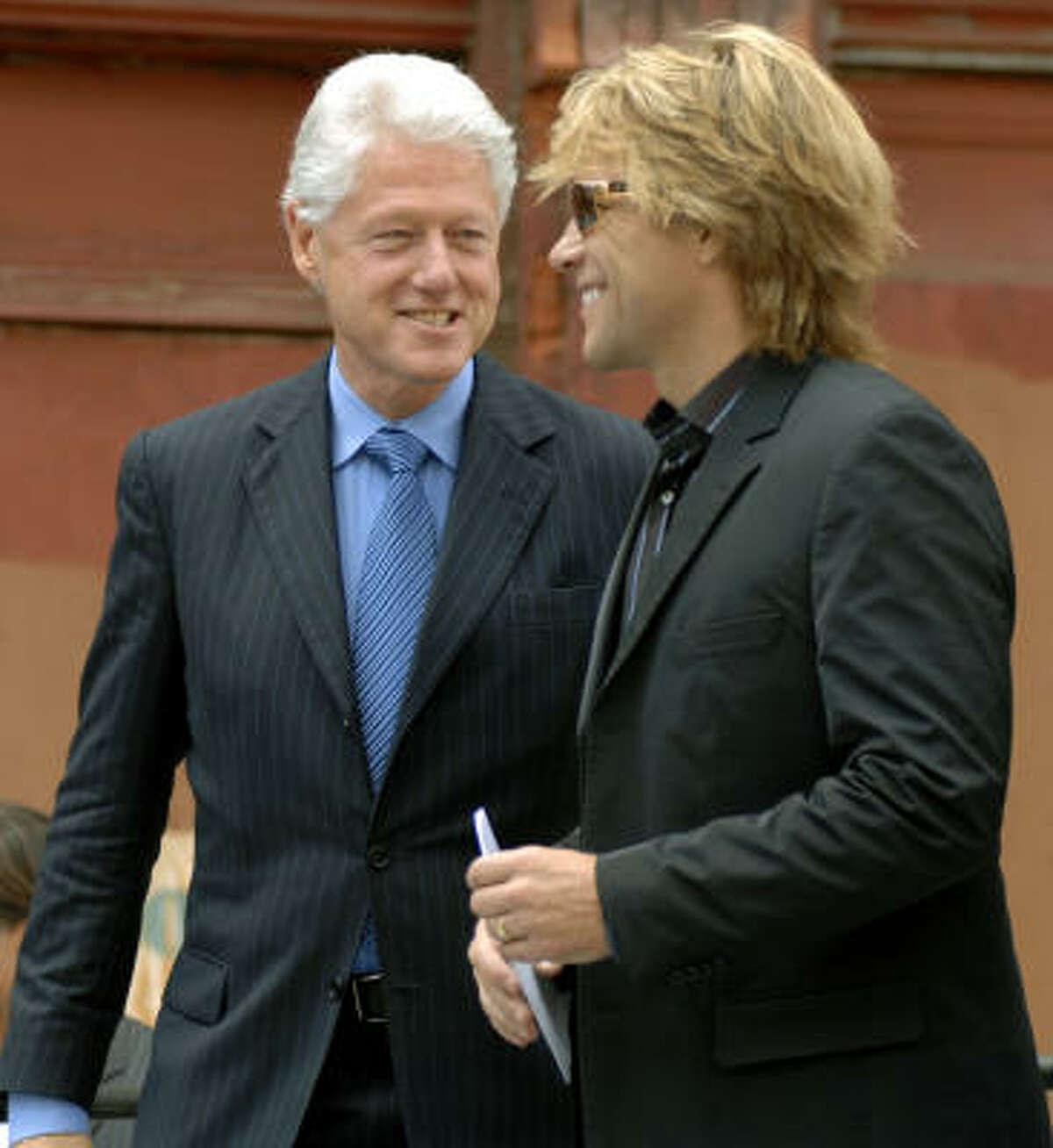 Former President Clinton, left, joins Jon Bon Jovi as the musician announces the program.