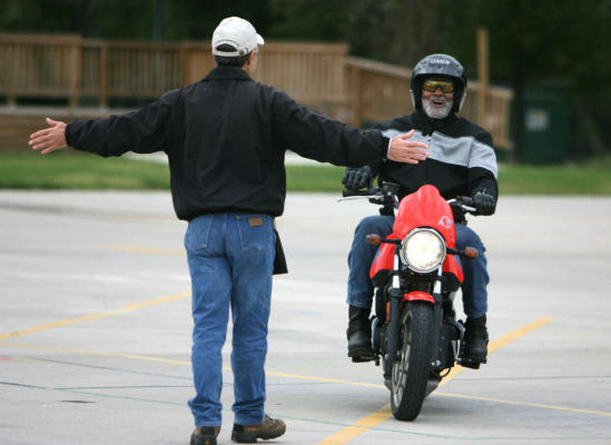 Anthony McGill, right, gets feedback from instructor Mike Gately during a motorcycle safety class.