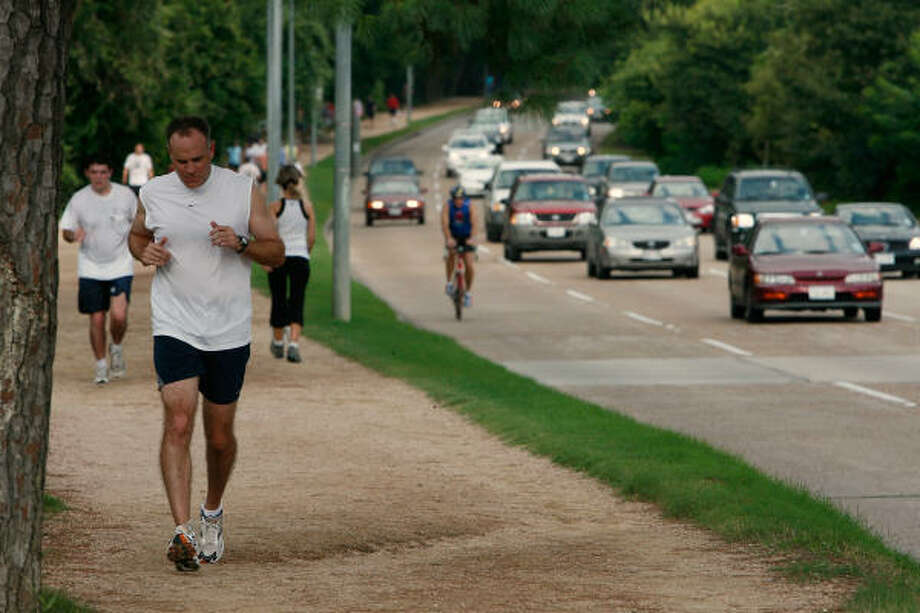 Runners and walkers circle the Memorial Park running path along Memorial Drive on Aug. 2.  Health benefits from exercising may be negated by the nearby automobile exhaust. Photo: Kevin Fujii, Chronicle