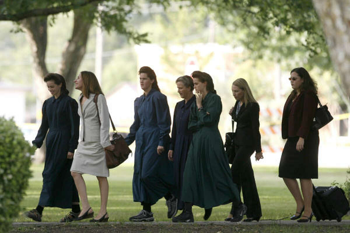 Members of the Fundamentalist Church of Jesus Christ of Latter Day Saints walk with attorneys to the Schleicher County Courthouse in Eldorado last month, when the grand jury opened its investigation of the polygamist sect.